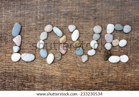 colorful arrangement of stones with a form of the word love on background wood texture - stock photo