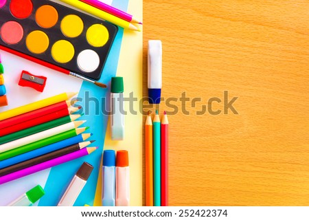 Colorful art supplies on a school desk with space for text - stock photo