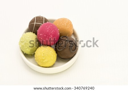 Colorful assortment of chocolate balls.  Different colors for variety of fruits flavor on a white ceramic plate.  Isolated on white background. - stock photo