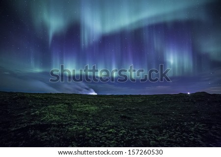 Colorful aurora over a mossy Icelandic lava field  - stock photo
