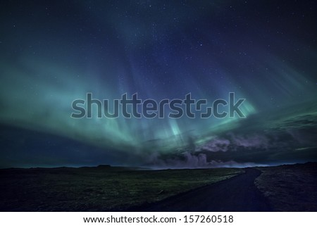Colorful aurora over a road through an Icelandic lava field. - stock photo