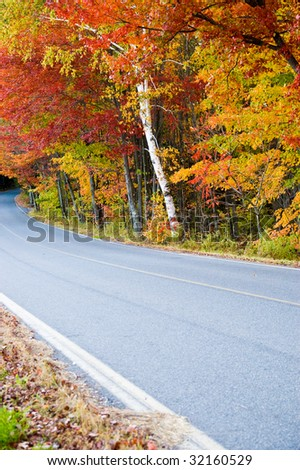 Colorful autumn foliage along a country road in New England - stock photo