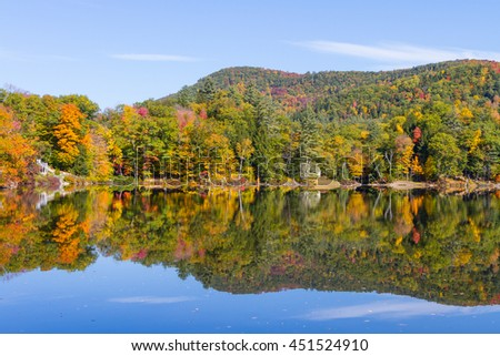 colorful autumn foliage by lake side in the Lake Rescue, vermont