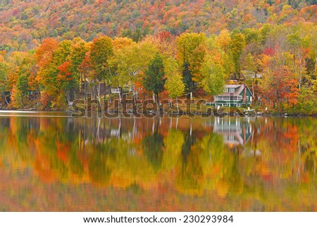 colorful autumn foliage by lake side in vermont - stock photo