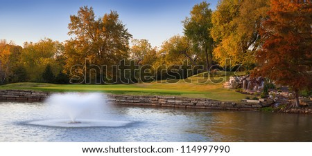 Colorful Autumn landscape with a flowing fountain in the water. - stock photo
