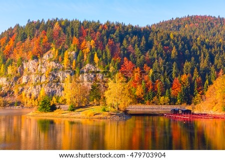 Colorful autumn mountain landscape with multicolored trees, blue sky and reflection in the water, National park Slovak paradise (Narodny park Slovensky Raj), Slovakia