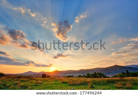 Colorful autumn sunset with sun rays coloring the clouds - stock photo