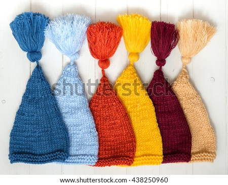 colorful baby knitted hats folded in row on white painted table, top view - stock photo
