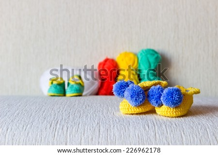 Colorful baby shoes with colored wool on white background - stock photo