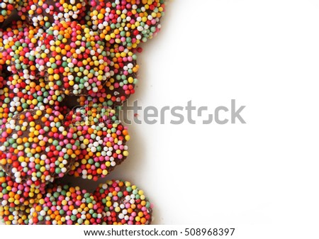 Colorful background of chocolate freckles on white