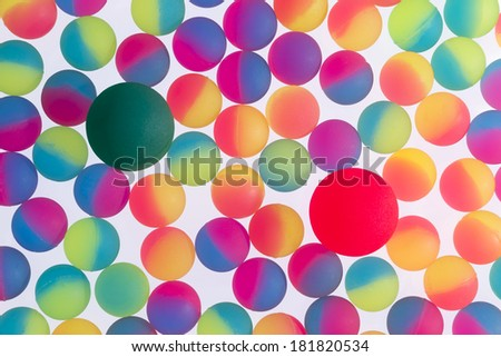 Colorful background of illuminated bicolor plastic balls in the colors of the rainbow arranged in a single full frame layer on a white background - stock photo