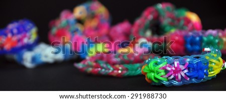 colorful background rainbow colors rubber bands loom bracelets on black background - stock photo