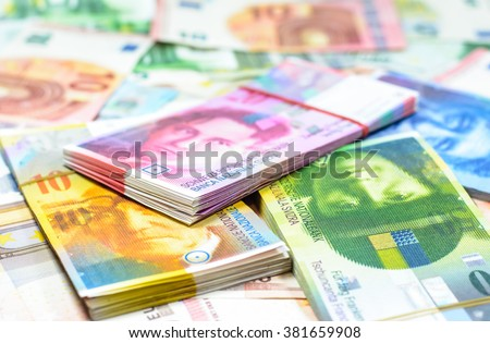 Colorful background with swiss franc currency,money.Focus on eye green banknote and blurry on euro background - stock photo