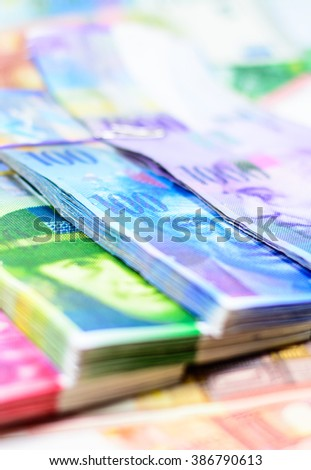 Colorful background with swiss franc currency,money.Focus on eye of blue 100  banknote and blurry on euro background