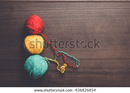 colorful ball of threads on wooden background - stock photo