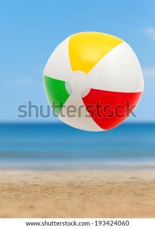 Colorful ball on a sandy beach - stock photo