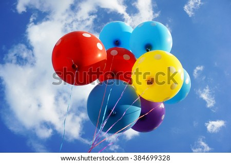 Colorful balloons against sunny blue sky.