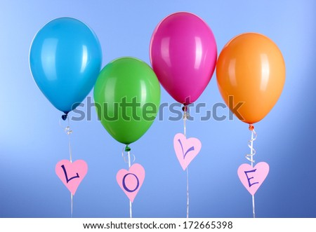 "Colorful balloons keeps word ""love"" on blue background"