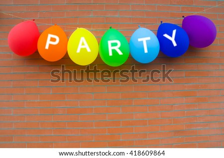 Colorful balloons of rainbow colors with party word on brick wall