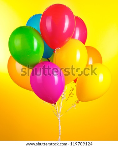 Colorful balloons on yellow background - stock photo