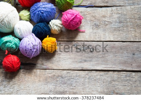 Colorful balls of wool on a wooden background - stock photo