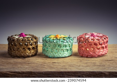 Colorful bamboo baskets on wooden table - stock photo