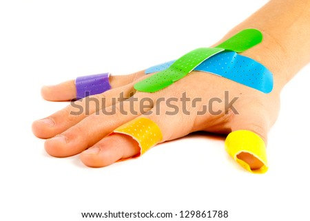 Colorful bandages on child's hand. - stock photo