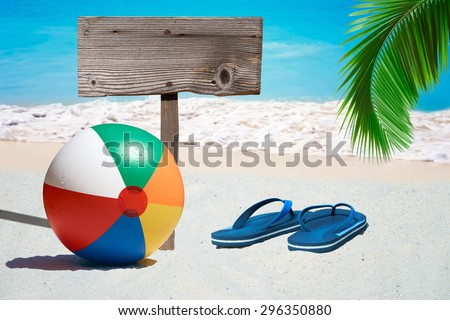 Colorful Beach Ball, Flip Flops and a wooden Signboard on the Beach