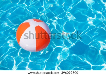 Colorful beach ball floating in a pool - stock photo
