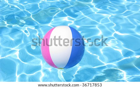 Colorful beach ball floating on the swimming pool.
