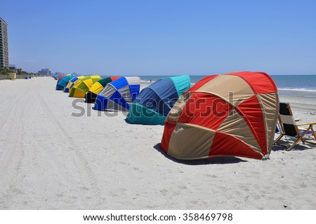Colorful beach cabana line the beach shielding beach lovers from the sun and wind.  - stock photo