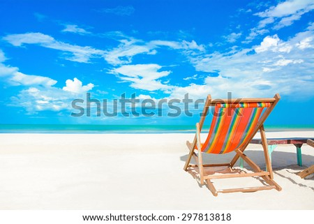 Colorful beach chair on white sand beach in bright blue sky background - summer holiday and vacation concepts