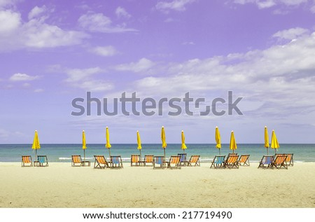 Colorful beach chairs and closed umbrellas on beautiful beach with cloudy blue sky. Concept for rest, relaxation and holiday in Thailand. - stock photo