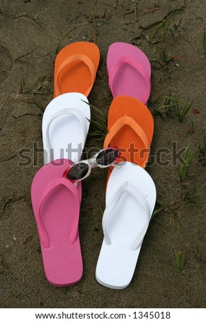 colorful beach shoes and sunglasses on sand