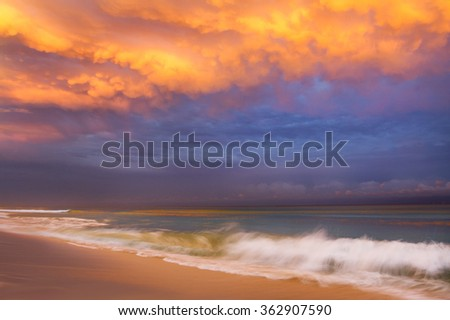 Colorful beach sunset with dramatic looking clouds over the sand and ocean