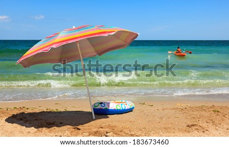 Colorful beach umbrella and inflatable toy boat at sea