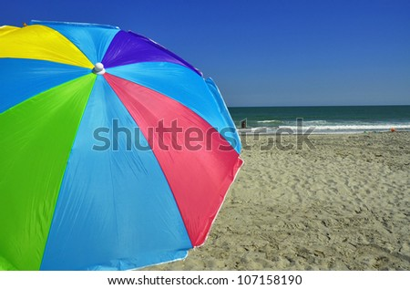Colorful Beach Umbrella at beach, room for your text - stock photo