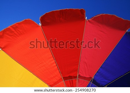 colorful beach umbrella edge with blue sky background - stock photo