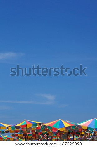 colorful beach umbrellas on a sunny day (minimal style) - stock photo