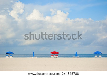 Colorful beach umbrellas on tropical Clearwater Beach with uncluttered sand and sky area for text. - stock photo