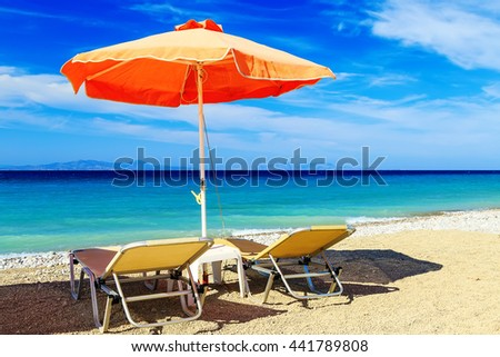 colorful beach umbrellas with deck chairs pebble beach and island in the distance