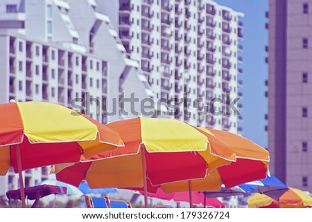 Colorful beach umbrellas with hotels in background.