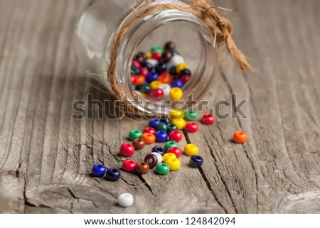 colorful beautiful glass beads with glass jar on old wooden table - stock photo