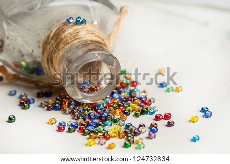 colorful beautiful glass beads with vintage glass bottle on white wooden table - stock photo