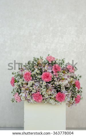Colorful beauty flower arrangement centerpiece in square white vase in white wall background. Image can use design for valentine card or greeting to wedding decoration - stock photo