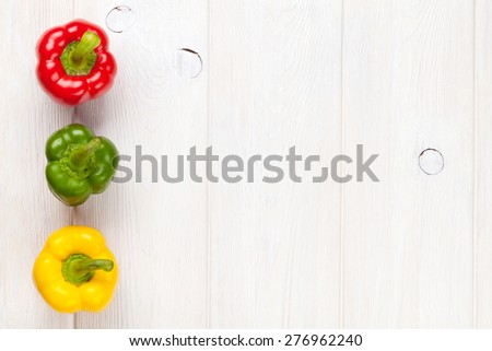 Colorful bell peppers on white wooden table. Top view with copy space - stock photo