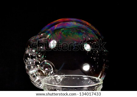 colorful big soap bubble with black reflective background