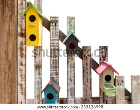 colorful bird box on wooden fence isolated on white background - stock photo