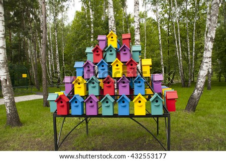 Colorful birdhouses in the park among the birches
