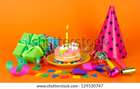 Colorful birthday cake with candle and gifts on orange background